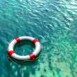 Lifesaver on clear blue and green water surface. Digital illustration. — Stock Photo #2721127