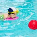 Child in swimming pool, kid swim playing water ball, boy indoor training — Stock Photo #3519918