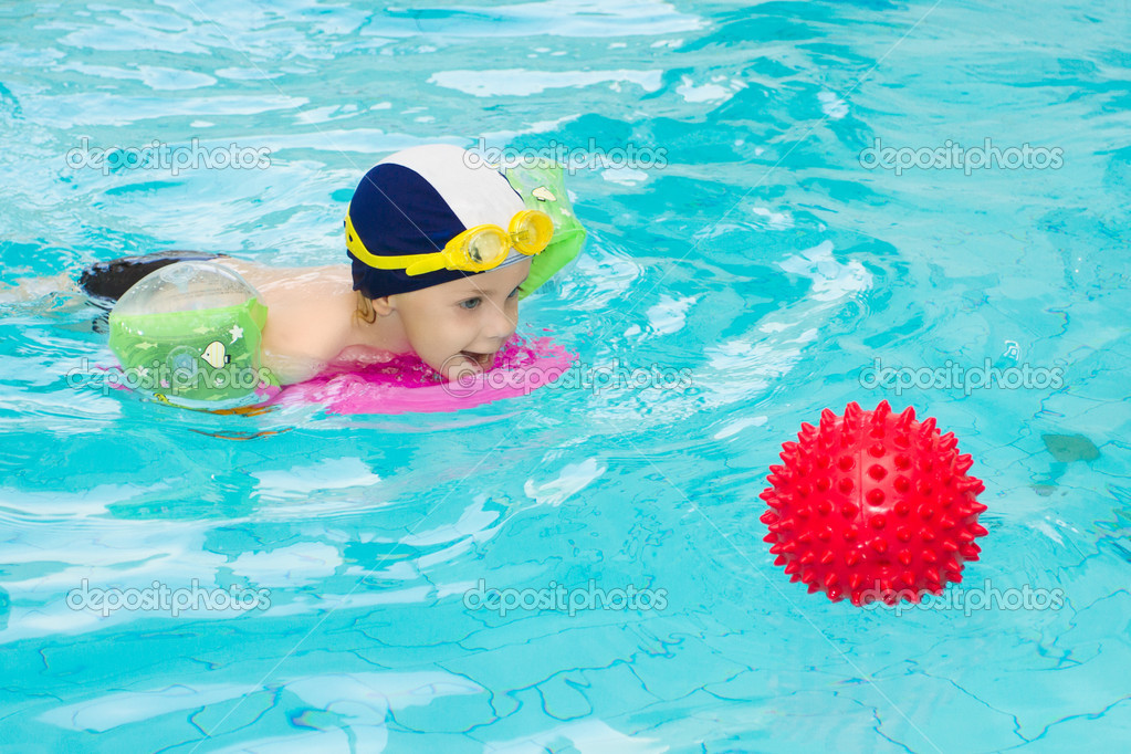 3 year old child playing with red ball in the swimming pool — Stock Photo #3519918