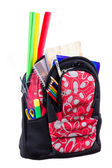 Black and red packback with school supplies — Stok fotoğraf