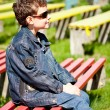 Cool boy sitting in a park — Stockfoto