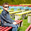 图库照片: Cool boy sitting in a park