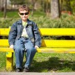 Cool kid sitting on bench - Zdjęcie stockowe