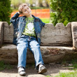 Cute kid sitting on bench - Stock Photo