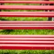Red benches in a park - Foto Stock