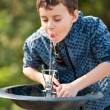 Cute kid drinking water in a park — Stock fotografie