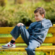 Cute schoolboy in a park — Stock fotografie
