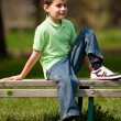 Cute little boy sitting on a bench — Stock Photo #2894585
