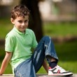 Cute little boy sitting on a bench — Stock Photo