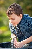 Cute kid drinking water in a park — Stock fotografie