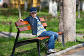 Kid on a bench outdoors — Stock Photo