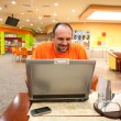 Man with laptop in restaurant — Stock Photo