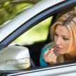 Young lady applying makeup in car — Stock Photo #3222177