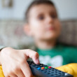 Holding tv remote control — Stock Photo