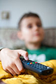 Holding tv remote control — Stock Photo
