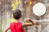 Child playing darts — Stock Photo