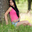 Girl leaning on a tree -  
