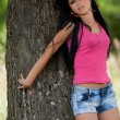 Girl leaning on a tree - Stok fotoraf