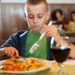 Little boy eating in a restaurant - Stok fotoğraf