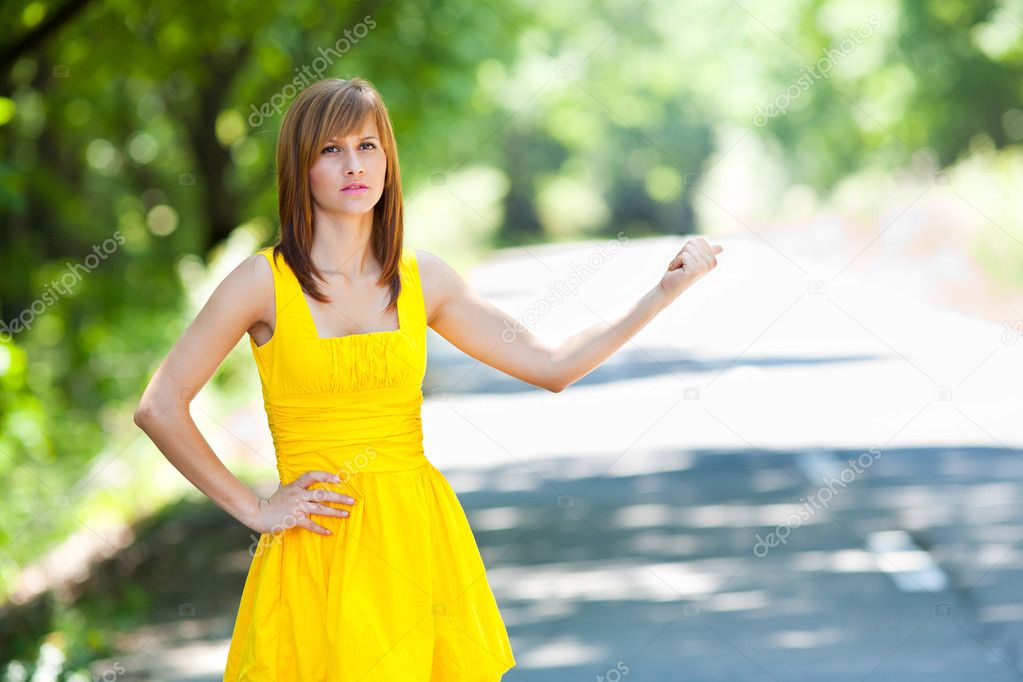 Beautiful blonde woman in yellow dress trying to stop the car on road, hitchhiker  Stock Photo #3548807