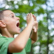 Little boy shouting in the forest - Stock Photo