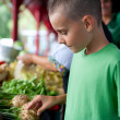 Cute boy buying vegetables - Stock Photo