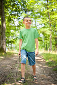 Cute boy walking through the forest — Stock Photo