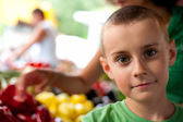 Cute boy buying vegetables — Stock Photo