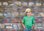 Cute child leaning on a wall — Stock Photo