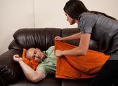 Mujer cubre a su marido con una manta — Foto de Stock