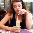 Young woman drinking soda in a restaurant — Stock Photo #3616703