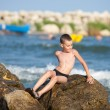 Little boy sitting on rocks at sea — Stock Photo