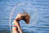 Hermosa jovencita salpicar con su cabello — Foto de Stock
