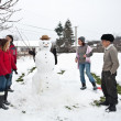 Happy family around a snowman - Stock Photo