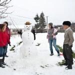 Happy family around a snowman — Stock Photo