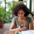 Stock Photo: Young woman using cellphone in a restaurant