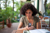 Young woman using cellphone in a restaurant — Stock Photo
