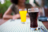 Glass with coke and lady in background — Stock Photo