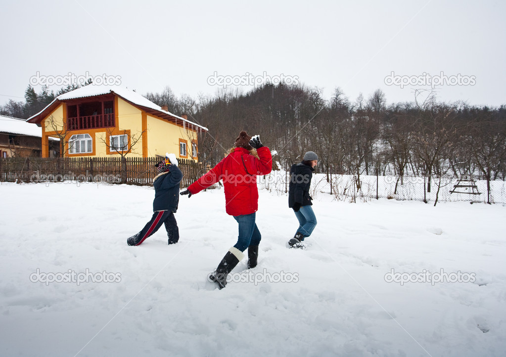 Young family having fun with a snowball fight during winter holiday — Stock Photo #3735831