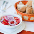 Stock Photo: Tomato and onions salad with bread in background