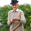 Stock Photo: Old rural man using scythe
