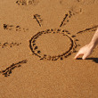 Hand drawing a sun in the sand — Stockfoto