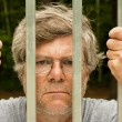 Man behind bars - Stock Photo