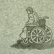Stock Photo: Stone carving of min wheelchair