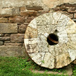 Stock Photo: Old millstone leaning on a wall