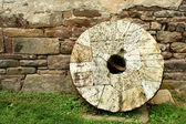 Old millstone leaning on a wall — Stock Photo