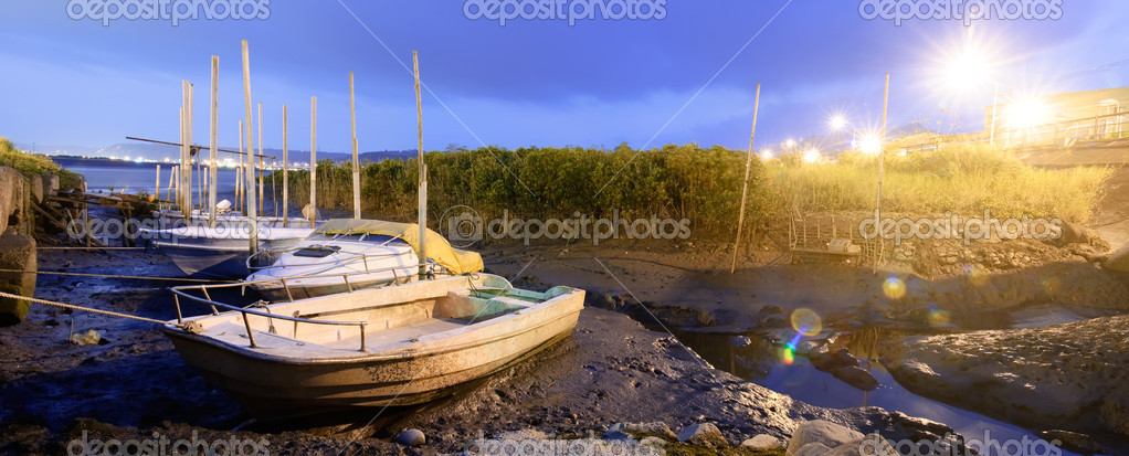 Discard boats on silt of river with city light flare in night. — Stock Photo #2918222