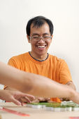 Happy smiling Asian man play Mahjong — Stock Photo