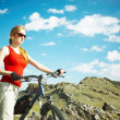 The girl with a bicycle against mountains — Stock Photo