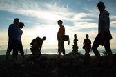Silueta del grupo de en la parte superior de la montaña contra una disminución — Foto de Stock